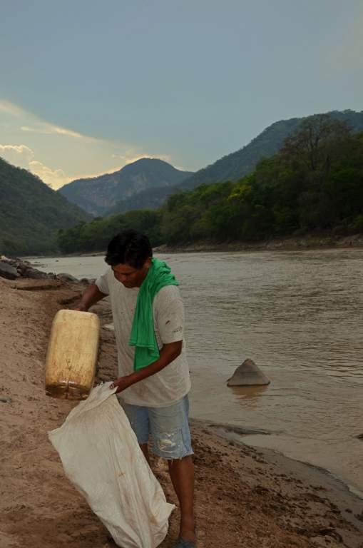 Don Justino Ayala recoge agua del Río Grande