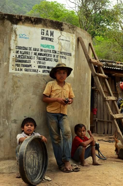 Roberto Carlos y sus hermanos junto al tanque de cosecha de agua