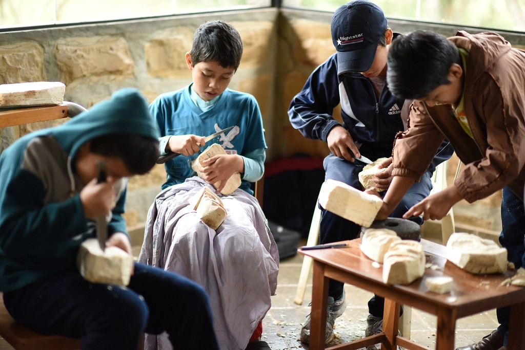 Durante su aprendizaje, los pequeños artesanos utilizaron pedazos de raíz de toco del tamaño de una cabeza, que limpiaron con un cuchillo y poco a poco le dieron forma de un rostro.