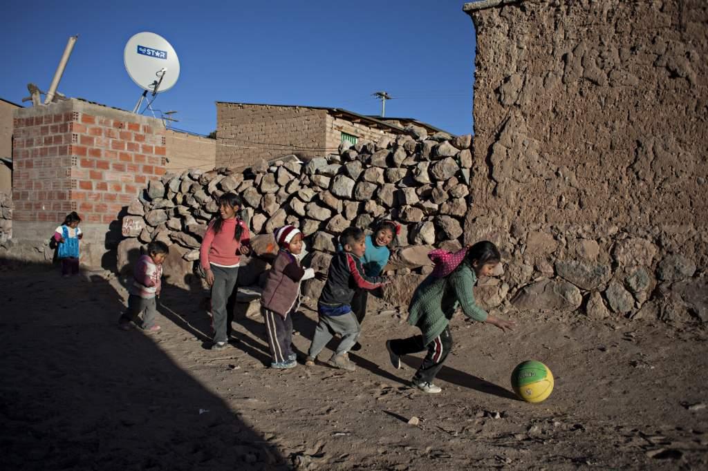 Algunos niños juegan con una pelota en una calle polvorienta de Orinoca. Foto: Patricio Crooker ©